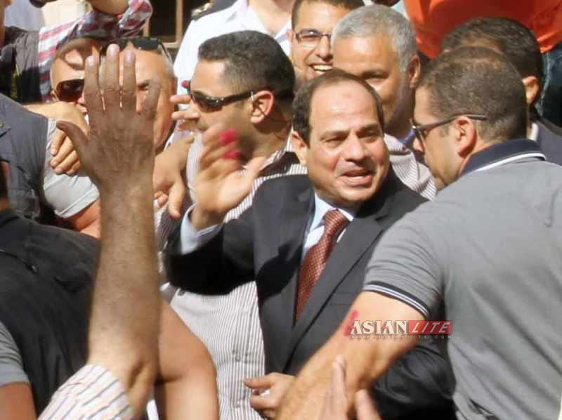 Presidential candidate Abdel-Fattah al-Sisi(2nd R) waves to supporters at a polling station in Cairo, Egypt