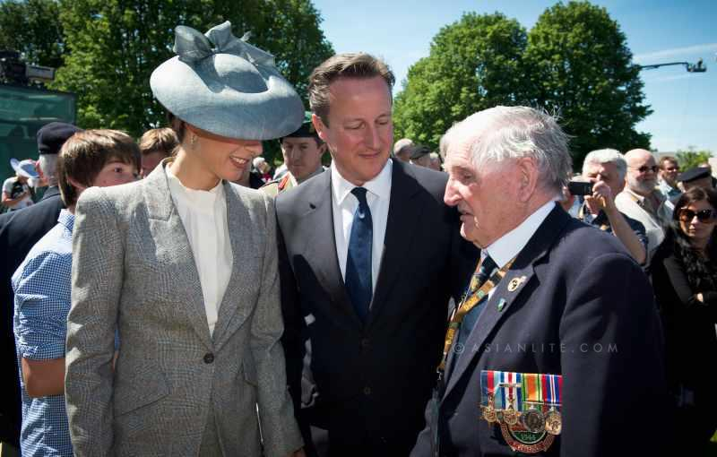 British Prime Minister David Cameron and wife Samantha with a war veteran during the D-Day events