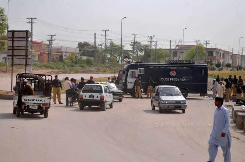 Policemen stop vehicles on the way to Islamabad airport in Rawalpindi, Pakistan, June 23, 2014. Pakistani authorities on Monday denied permission to a plane carrying an anti-government religious leader to land at Islamabad airport over security concerns