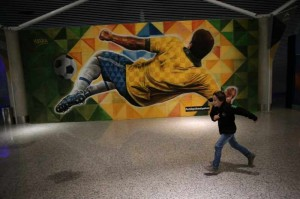A boy runs in front of a football-themed mural inside the Brasilia International Airport in Brasilia