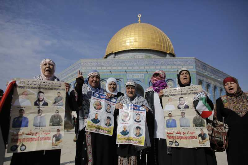 Palestinian protesters shout slogans and hold portraits of relatives incarcerated in Israeli jails during a demonstration in solidarity with Palestinian prisoners outside Jerusalem's Dome of the Rock mosque at the Al-Aqsa mosque's compound, in Jerusalem's old city,