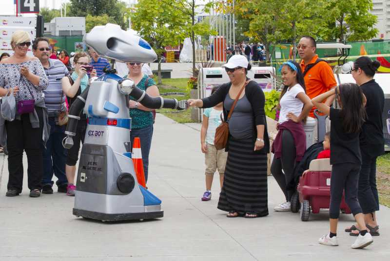 TORONTO:- A robot shakes hands with a woman during the 2014 Canadian National Exhibition in Toronto, Canada, Aug. 15, 2014. Kicked off on Friday, the 18-day event is expected to attract more than one million visitors from around the world. (Xinhua/Zou Zheng)