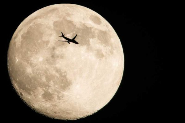 In the Egyptian capital Cairo over an airplane flying over the full moon.
