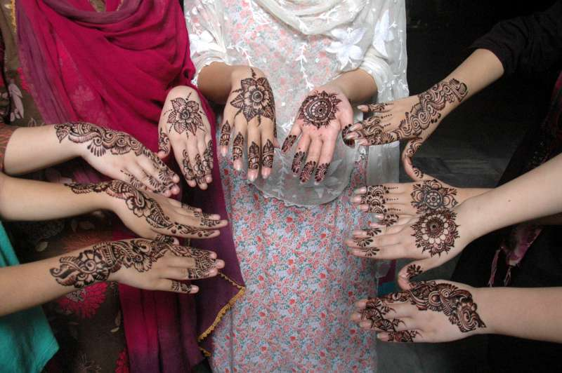 Pakistani girls show their hands painted with henna