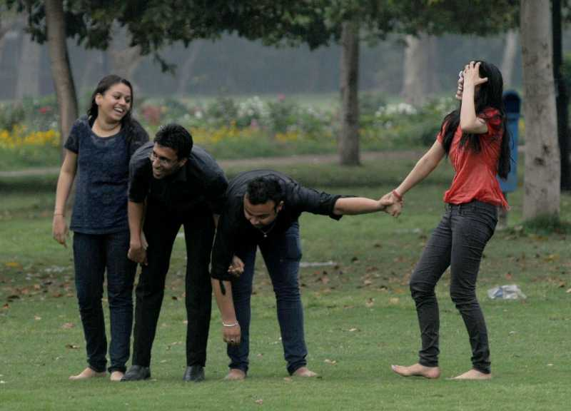 People enjoy themselves after rains at India Gate lawns in New Delhi on March 28, 2014. (Photo: IANS)
