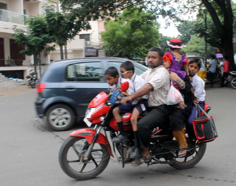 A man rides with six persons including 4 children on his bike in Hyderabad on Aug 12, 2014. (Photo: IANS)