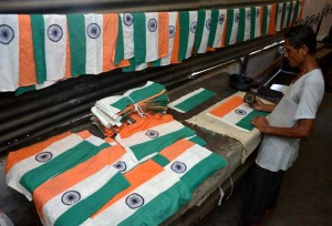 Workers make the national flag ahead of Independence Day in Guwahati on Aug 8, 2014. (Photo: IANS)