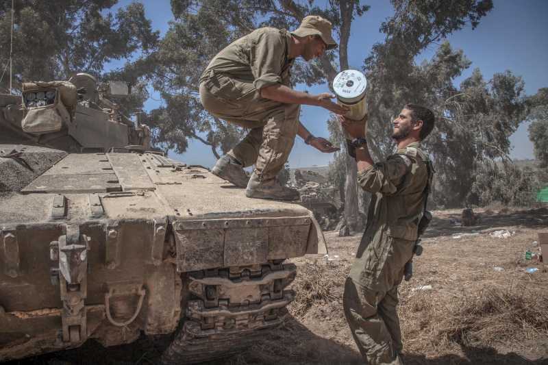 An Israeli soldier hands a shell to another on a Merkava tank at an army deployment area in southern Israel near the border with Gaza