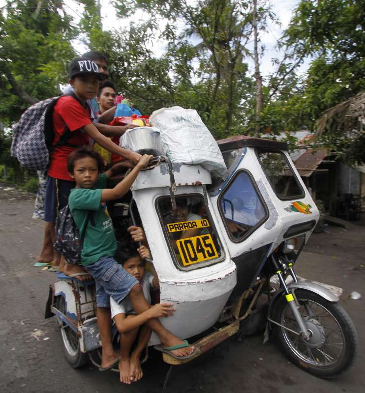 """Residents crowd on a tricycle as they evacuate from the danger zone near the Mayon Volcano in Albay Province, the Philippines, Sept. 17, 2014. The Philippine Institute of Volcanology and Seismology (PHIVOLCS) said Wednesday that Mayon Volcano in the eastern Philippine province of Albay has exhibited """"intense activity"""" based on its 24-hour observation. The Philippine military said that more than 2,000 families or 10,000 individuals from five municipalities near the volcano have already been transferred to various evacuation centers."""