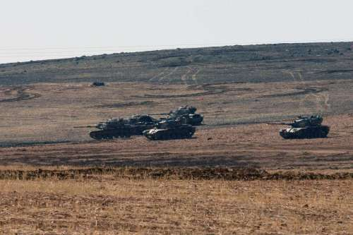 Turkish army tanks take position on the Turkish side of the Turkish-Syrian border . The Turkish security forces have taken strict security measures along the Turkish-Syrian borderline to prevent infiltrations from Syria into Turkey's territory.