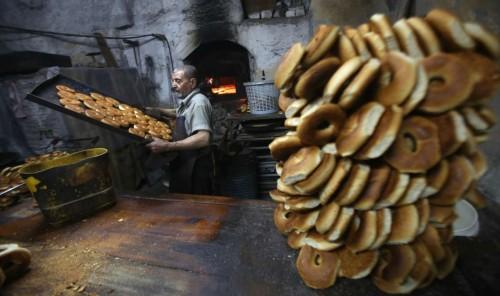 Palestinian baker Darwish Abu Samra, 77, bakes Shami cakes at his bakery in the West Bank City of Nablus
