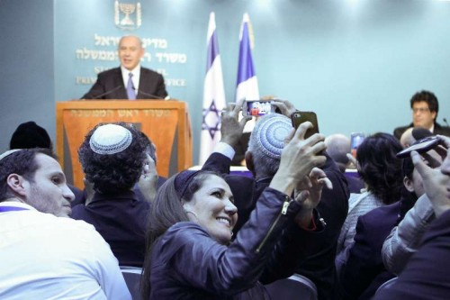 People take photos of a news conference addressed by Israeli Prime Minister Benjamin Netanyahu at the Prime Minister's office in Jerusalem, on Nov. 23, 2014. The Israeli cabinet on Sunday approved a controversial proposal which enshrines in law that Israel is the nation of the Jewish people amid growing tensions between Jews and Arabs.