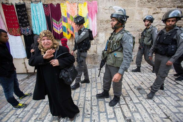 Palestinian women stand next to Israeli border police near a barrier leading to the Al-Aqsa Mosque near lions gate in Jerusalem's Old City (File)