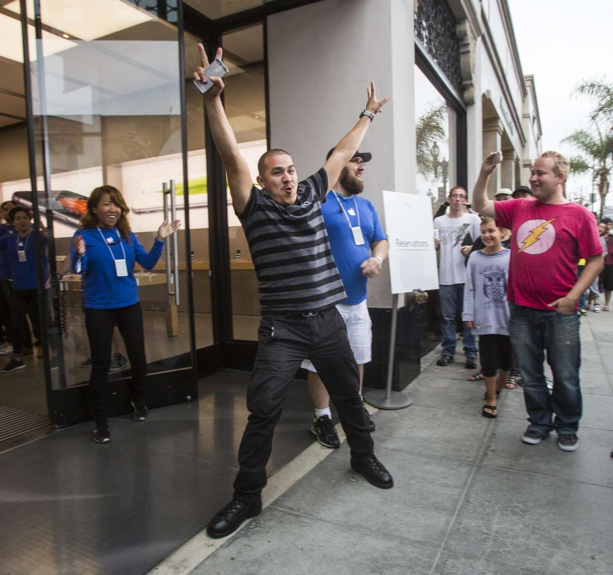 An Apple fan celebrates for being the first person purchasing an iphone 6 smartphone at an Apple store in Los Angeles, California