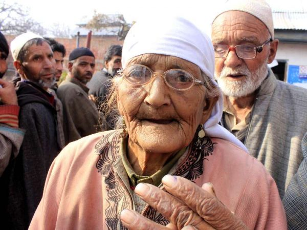 A 95-year old lady arrives at a polling booth to cast her vote during the third phase of Jammu and Kashmir polls