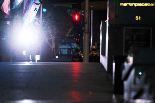 Policemen secure Martin Place in Sydney, Australia, on Dec. 15, 2014. A gunman, who held an unknown number of people hostage in a downtown cafe in Martin Place of Sydney on Monday, has been identified after five hostages managed to flee the hours-long siege.