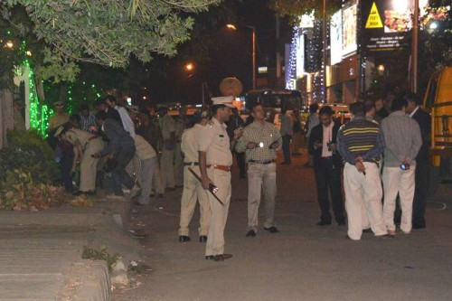 Policemen the site of the low intensity bomb blast that rocked Church Street area of Bengaluru on Dec 28, 2014. Two people, including a woman, were injured in the blast near a food outlet in the city centre.