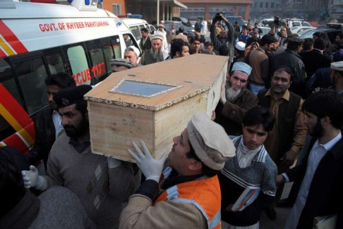 People carry a coffin of a student at a hospital in northwest Pakistan's Peshawar, Dec. 16, 2014.