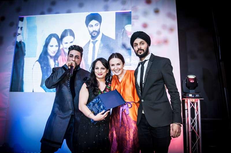 Kiran Singh holding the award