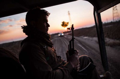 A Kurdish fighter sits in a vehicle heading to the front line with so-called Islamic State in southwest suburb of Kirkuk in the northern Iraq, Dec. 10, 2014.