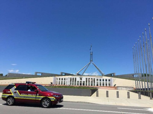 A police patrol car passes the forecourt of the Parliament House hours after a few gunmen took people hostage in a cafe in Sydney CBD, in Canberra, Australia, Dec. 15, 2014.