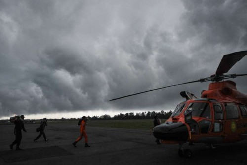Search and Rescue (SAR) team members bring body bags to helicopter in bad weather at Pangkalan Bun, in Central Kalimantan, Indonesia, Dec. 31, 2014. Indonesian authorities confirmed object and corpses spotted were from the missing AirAsia plane and they will continue to search on Wednesday.