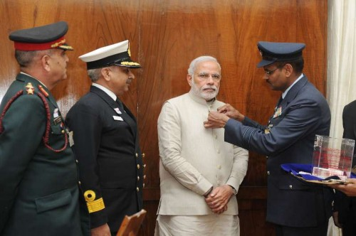 The Officers of the Kendriya Sainik Board pinning a flag on the Prime Minister, Shri Narendra Modi during the Armed Forces Flag Day, in New Delhi on December 04, 2014.