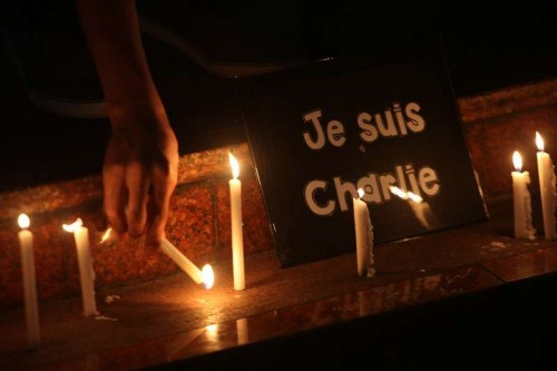 """A member of the National Union of Journalists of the Philippines (NUJP) lights candles in front of a placard that reads """"je suis Charlie"""" (I am Charlie) during a candle lighting ceremony in Quezon City, the Philippines, Jan. 9, 2015. The NUJP denounced the attack on French satirical magazine Charlie Hebdo which killed 12 people and wounded 11 others."""
