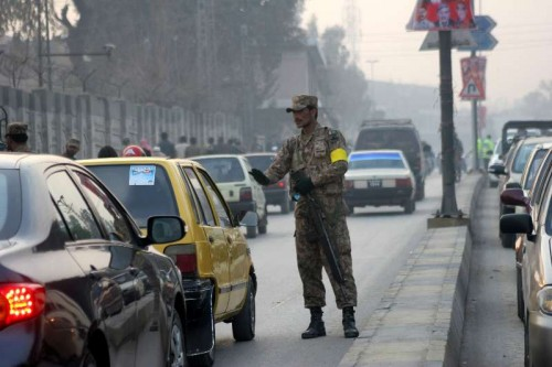 A Pakistani soldier stops vehicles near the Army Public School in northwest Pakistan's Peshawar, Jan. 12, 2015. Schools in Pakistan's northwestern city of Peshawar reopened on Monday for the first time since a Taliban raid massacred 150 people, mainly children, with returning students expressing defiance tinged with apprehension.
