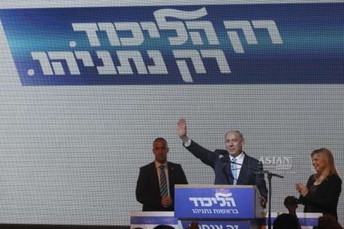 Israeli Prime Minister and Likud Party leader Benjamin Netanyahu  waves to supporters with his wife Sara  at Likud Party campaign headquarters in Tel Aviv, Israel, on March 18, 2015. Israel's incumbent Prime Minister Benjamin Netanyahu claimed victory following exit polls showing him tied with opposition center-left Zionist Union led by Isaac Herzog in Tuesday's parliamentary elections.