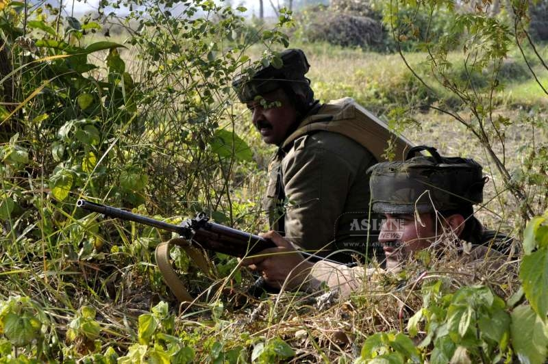 Soldiers take position during an encounter with militants who launched an attack on an army camp in Samba district of Jammu and Kashmir on March 21, 2015.