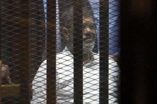 Egypt's ousted President Mohamed Morsi sits inside the defendants' cage at a court in Cairo, Egypt,