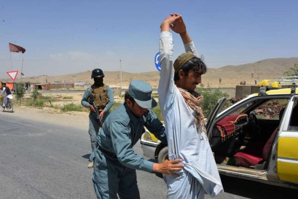 n Afghan policeman searches the body of a passenger at a police checkpoint in Ghazni province, Afghanistan, June 17, 2015