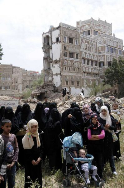 Yemeni women and children gather at the Old City of Sanaa, in Sanaa, Yemen, on June 16, 2015, where the historical buildings were damaged in the Saudi-led airstrikes. Protesters demand that all political parties reach an agreement to resume peace in the country at the Geneva talks.