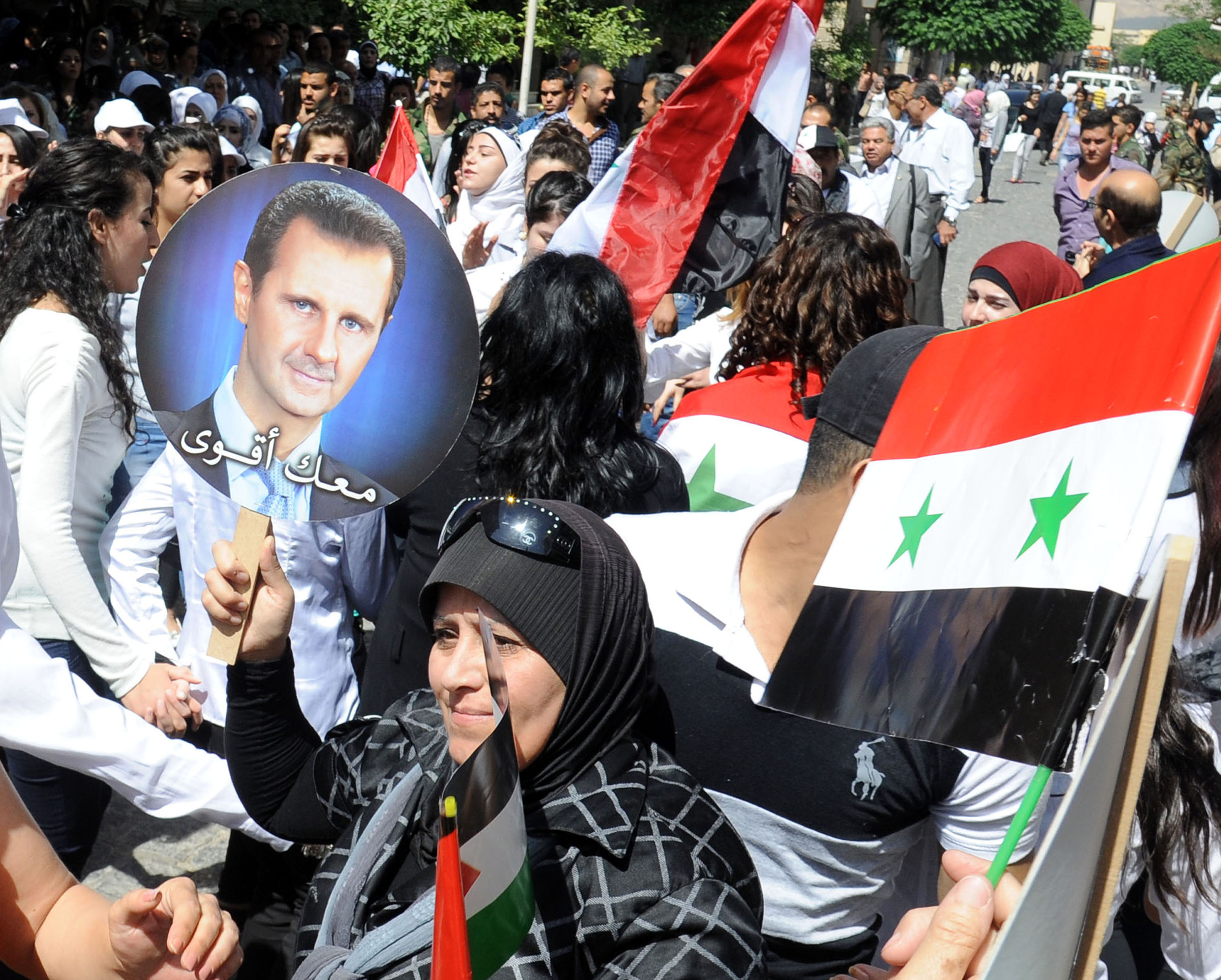 - Supporters of Syrian President Bashar al-Assad take part in a rally to celebrate the anniversary of Assad's reelection in Damascus on June 3, 2015. Assad won a third seven-year term in the presidential election last June, which was the first multi-candidate poll in Syria's modern history.