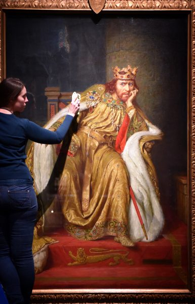 Alex Kavanagh, exhibition officer, polishes a painting of King John.The painting is part of the British Library's Magna Carta: Law, Liberty,Lecacy exhibition which will be opened until 1 September 2015. Photo by Clare Kendall, @C British Library