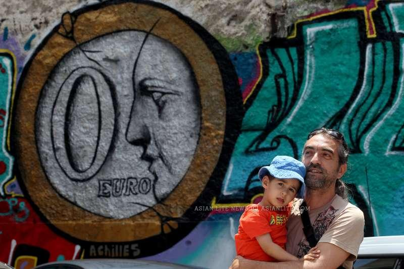 A man and a baby stand before a graffiti on a wall in central Athens, Greece, June 25, 2015. Graffiti artists express the anxiety felt by many Greeks amidst the uncertainty over the ongoing negotiations on the country's debt crisis