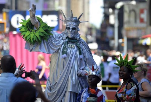 A street performer dressed as the Statue of Liberty pose with tourists for pictures in order to earn tips at Times Square in New York, the United States, on July 23, 2015. The number of Americans filing initial applications for unemployment benefits fell to a 42-year low last week in the latest sign the labor market is poised for further gains. First-time claims for the week ending July 18 dropped by 26,000 to 255,000, the lowest level since 1973, the Labor Department said