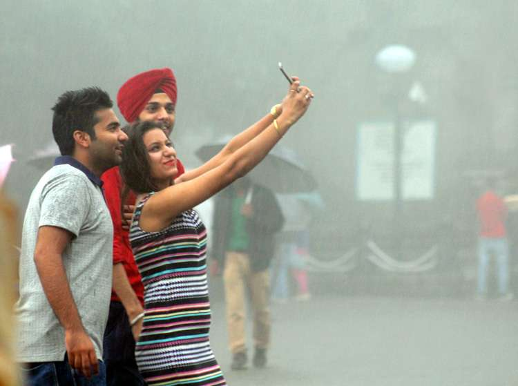 Teenagers taking a rain-drenched selfie in New Delhi