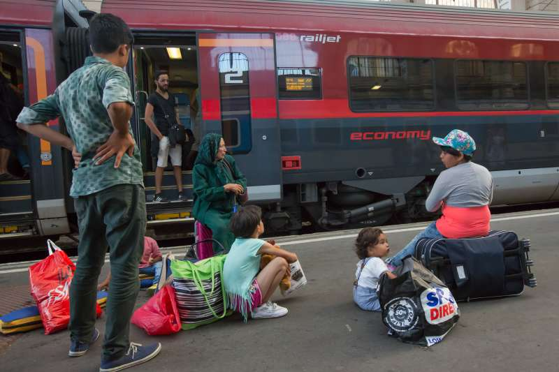 Travellers believed to be migrants wait for their train leaving for Austria, at Keleti railway station in Budapest, Hungary