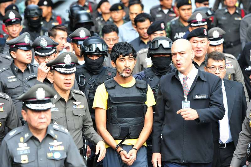 Yusufu Mieraili (C), one of the suspects in the Bangkok bombing, makes a crime re-enactment under escort of Thai police officers at a shopping center near Erawan Shrine in Bangkok, Thailand, Sept. 9, 2015. Yusufu Mieraili was arrested in Thailand's Sa Kaeo province near Cambodian border on Sept. 1