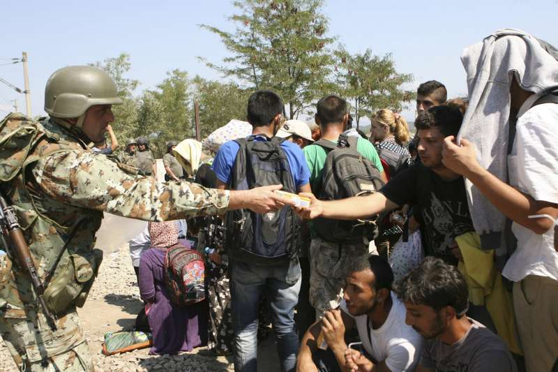 A Macedonian soldier gives juice to a refugee waiting to cross the border between Greece and Macedonia at a check point in Idomeni, Greece