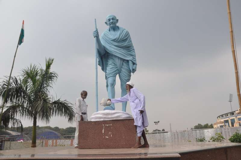 People clean a statue of Mahatma Gandhi on the eve of Gandhi Jayanti in Ranchi