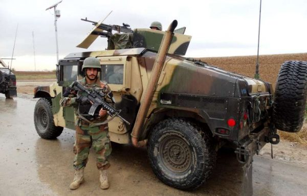 An Afghan army soldier stands guard near a military vehicle in Marjah district of southern Helmand province of Afghanistan