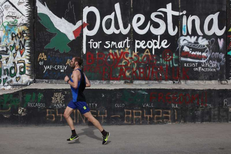 A participant runs next to the controversial Israeli barrier during the 3rd Palestine International Marathon in the West Bank city of Bethlehem on March 27, 2015. About 3,200 runners participated in the marathon this year, including about 750 foreigners and about 46 participants from the Gaza Strip, who participated for the first time (File)