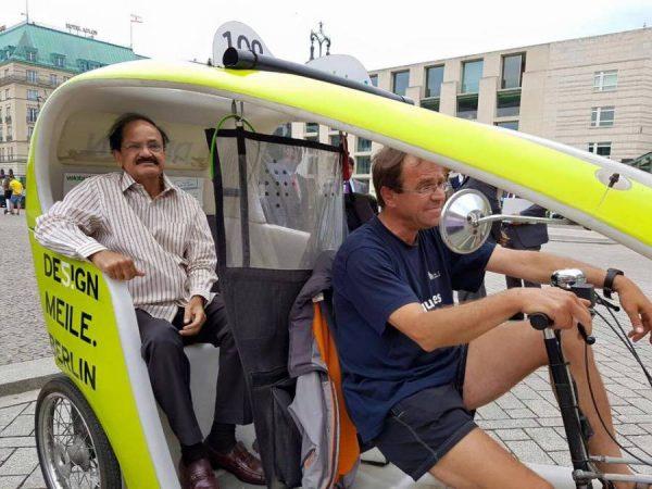 M. Venkaiah Naidu riding a German rickshaw in front of Brandenburg Gate, Berlin