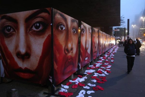 A woman walks in front of banners with photographs shown outside the Sao Paulo Museum of Art during a protest against the rape, abuse and violence against women in Sao Paulo, Brazil, on June 10, 2016. The protest demanding an end to the violence against women, refered to the allegedly mass rape of a 16-year-old girl that occurred in Rio de Janeiro