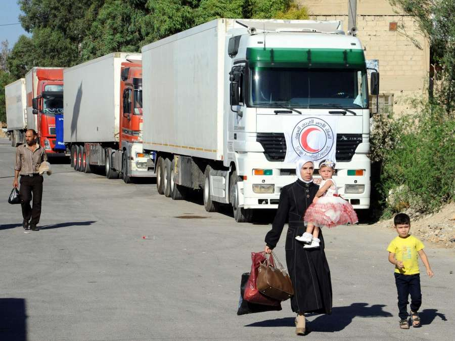 Civilians walk past aid convoy in the besieged town of Muadamiyeh, countryside of Damascus,