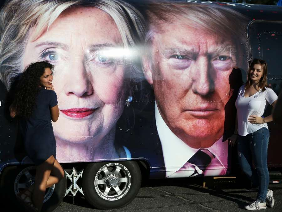 Supporters pose for photos with Hillary Clinton and Donald Trump posters at Hofstra University in New York, the United States on Sept. 26, 2016. The first of three presidential debates between the Democratic and Republican nominees, Hillary Clinton and Donald Trump, will be held Monday at Hofstra University in New York.