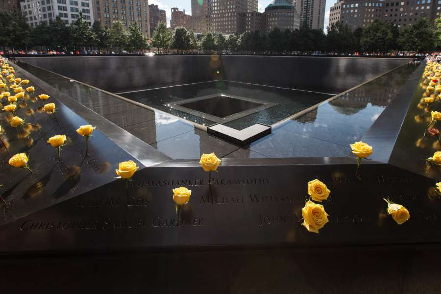 Flowers are placed on the names of the victims that are inscribed on parapets surrounding the north reflecting pool of World Trade Center 9/11 Memorial, in New York, the United States